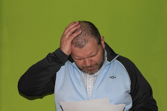 muž, papíry, držení za hlavu